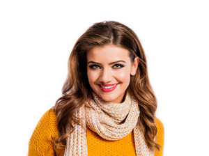 Beautiful young woman in mustard sweater. Studio shot on white background.