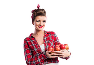 Beautiful young woman in red checked shirt with pin-up make-up and hairstyle holding a basket full of apples. Studio shot on white background. Autumn harvest