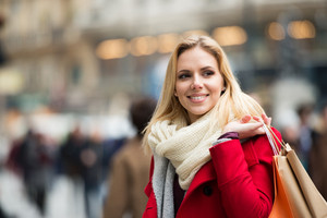 Beautiful young woman in red coat shopping in historical centre of the city of Vienna, Austria. Winter.