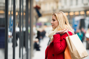 Beautiful young woman in red coat window shopping in historical centre of the city of Vienna, Austria. Winter.