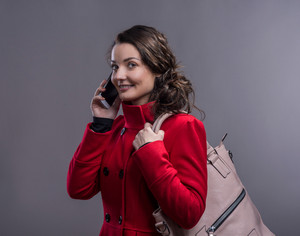 Beautiful young woman in red coat with smart phone. Studio shot on gray backgroung.