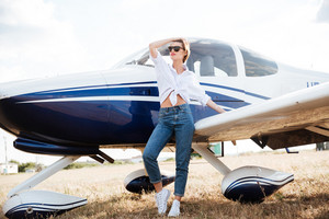 Beautiful young woman in sunglasses posing while standing near plane and looking away