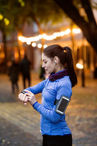 Beautiful young woman in the town in the evening with smart phone, smartwatch and earphones, listening music. Using a fitness app for tracking weight loss progress, running goal or summary of her run.