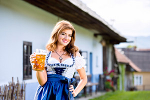 Beautiful young woman in traditional bavarian dress holding a mug of beer against old country house. Oktoberfest.
