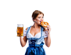 Beautiful young woman in traditional bavarian dress holding a mug of beer and pretzel, eating it. Oktoberfest. Studio shot on white background, isolated.