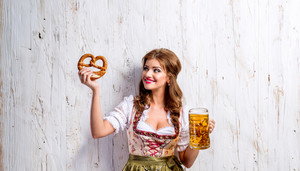 Beautiful young woman in traditional bavarian dress holding a mug of beer and pretzel. Oktoberfest. Studio shot on white wooden background.