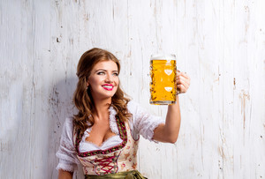 Beautiful young woman in traditional bavarian dress holding a mug of beer, clinking. Oktoberfest. Studio shot on white wooden background.