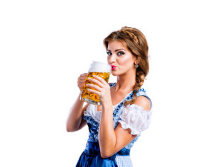 Beautiful young woman in traditional bavarian dress holding a mug of beer, drinking from it. Oktoberfest. Studio shot on white background, isolated.