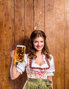 Beautiful young woman in traditional bavarian dress holding a mug of beer. Oktoberfest. Studio shot on brown wooden background. Copy space.