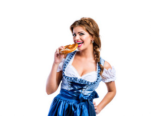 Beautiful young woman in traditional bavarian dress holding a pretzel, eating it, hand on hip. Oktoberfest. Studio shot on white background, isolated.