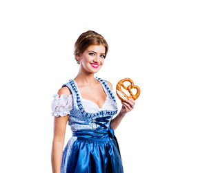 Beautiful young woman in traditional bavarian dress holding a pretzel. Oktoberfest. Studio shot on white background, isolated.
