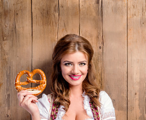 Beautiful young woman in traditional bavarian dress holding pretzel. Oktoberfest. Studio shot on brown wooden background. Copy space.