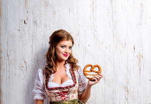 Beautiful young woman in traditional bavarian dress holding pretzel. Oktoberfest. Studio shot on white wooden background. Copy space.