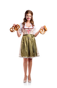 Beautiful young woman in traditional bavarian dress holding pretzels. Oktoberfest. Studio shot on white background, isolated.