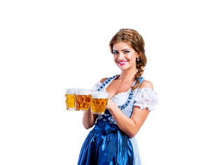 Beautiful young woman in traditional bavarian dress holding three mugs of beer. Oktoberfest. Studio shot on white background, isolated.