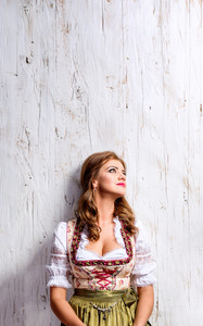 Beautiful young woman in traditional bavarian dress, Oktoberfest. Studio shot on white wooden background. Copy space.