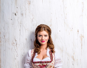Beautiful young woman in traditional bavarian dress, Oktoberfest. Studio shot on white wooden background.