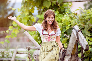 Beautiful young woman in traditional bavarian dress sitting on old wooden horse. Oktoberfest.