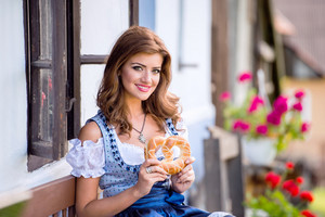 Beautiful young woman in traditional bavarian dress sitting on wooden bench holding pretzel, against old country house. Oktoberfest.