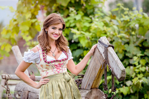 Beautiful young woman in traditional bavarian dress standing by an old wooden horse. Oktoberfest.