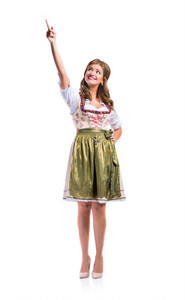 Beautiful young woman in traditional bavarian dress standing, hand on hip, pointing up. Oktoberfest. Studio shot on white background, isolated.
