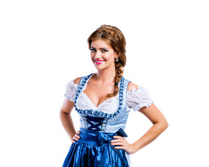 Beautiful young woman in traditional bavarian dress standing, hands on hips. Oktoberfest. Studio shot on white background, isolated.