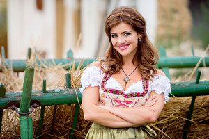 Beautiful young woman in traditional bavarian dress standing in front of wooden cart with dried hay. Oktoberfest.