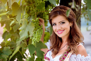 Beautiful young woman in traditional bavarian dress standing in the garden, holding a bunch of grapes, smiling.