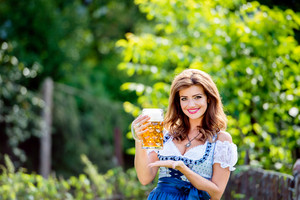 Beautiful young woman in traditional bavarian dress standing in the garden holding a mug of beer. Oktoberfest.