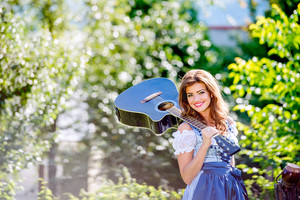 Beautiful young woman in traditional bavarian dress standing in the garden next to the wooden fence, holding guitar. Oktoberfest.