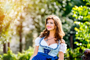Beautiful young woman in traditional bavarian dress standing in the garden. Oktoberfest.