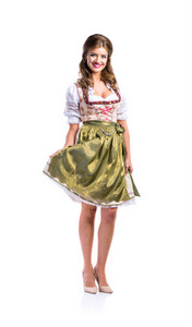 Beautiful young woman in traditional bavarian dress standing. Oktoberfest. Studio shot on white background, isolated.