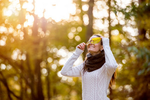 Beautiful young woman in white woolen knitted sweater in autumn forest covering her eyes with yellow tree leaves