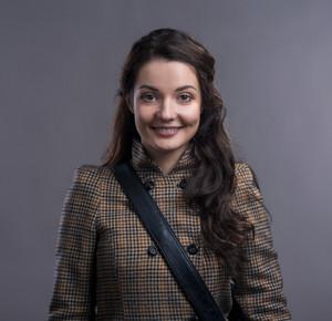 Beautiful young woman in winter coat. Studio shot on gray backgroung.