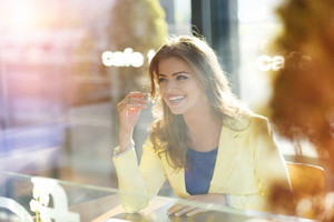 Beautiful young woman in yellow jacket sitting in cafe
