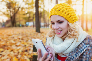 Beautiful young woman in yellow knitted hat, white scarf and checked coat holding smart phone, texting. Sunny autumn park.