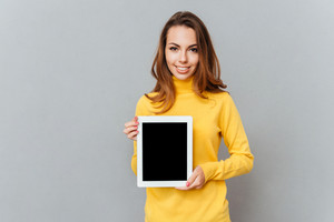 Beautiful young woman in yellow sweater showing tablet computer with blank screen isolated on a gray background