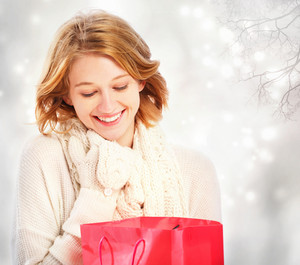 Beautiful young woman looking at a red gift bag