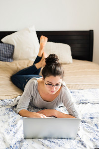 Beautiful young woman lying on bed, working on notebook, home office.