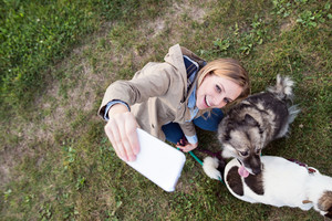 Beautiful young woman on a walk with a dog in green sunny nature, taking selfie with smart phone.
