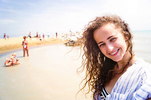 Beautiful young woman on beach wearing striped blue and white shirt, smiling, taking selfie. Enjoying time at seaside.