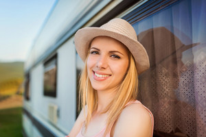 Beautiful young woman outside the camper van on a summer day