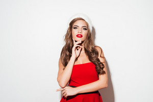 Beautiful young woman posing in red santa claus costume and hat isolated over white background