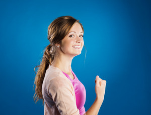 Beautiful young woman posing in studio over a blue background