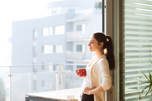 Beautiful young woman relaxing on balcony with city view holding cup of coffee or tea