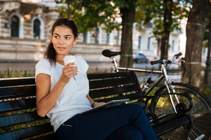 Beautiful young woman resting on the bench with cup of coffee at the city park