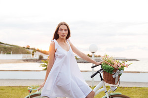 Beautiful young woman riding bicycle with flower basket on promenade