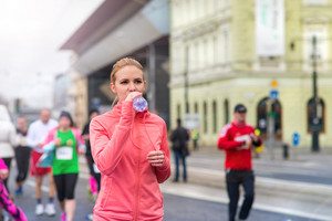 Beautiful young woman running in the city competition drinking water at the refresment point