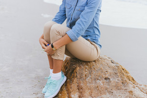 Beautiful young woman sitting on a rock by the sea. She is dressed in beige trousers and a denim shirt. Walking in the fresh air.