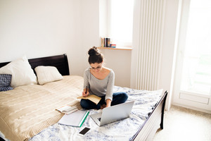 Beautiful young woman sitting on bed, working on laptop, writing something into her notebook, home office.